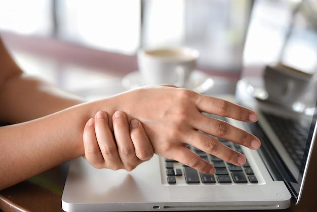Mulher do close up que guarda sua dor da mão de usar muitos tempos do computador. conceito de síndrome de escritório.