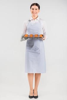 Mulher do cozinheiro chefe da pastelaria que guarda queques