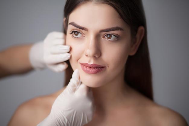 Mulher do cuidado de pele que remove a composição da cara - cuidado de pele.