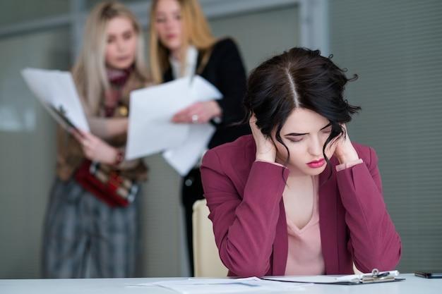 Mulher do escritório cansada do espaço de trabalho barulhento