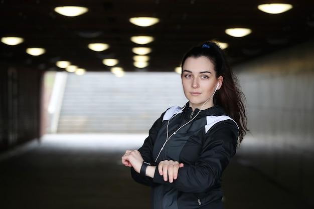 Mulher do esporte ao ar livre olhando seu relógio de pulso