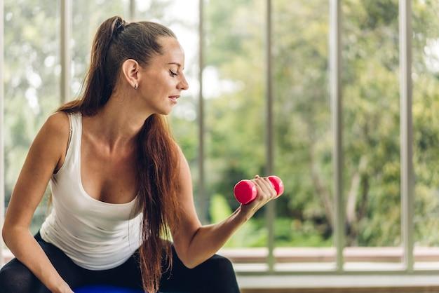 Mulher do esporte em roupas esportivas sentada relaxando e fazendo exercícios de fitness com halteres na academia