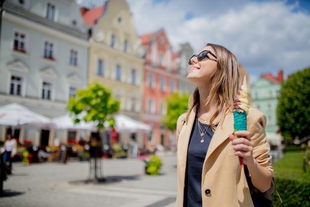 Mulher do estilo nos óculos de sol e no gelado no quadrado envelhecido do centro de cidade.