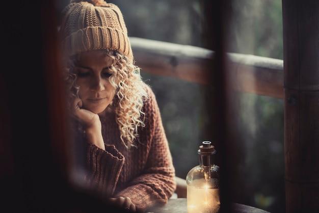 Mulher do lado de fora de casa no inverno, através de uma janela