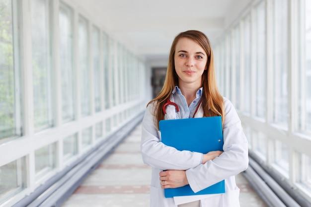 Mulher do médico sobre o fundo dos interiers da clínica.