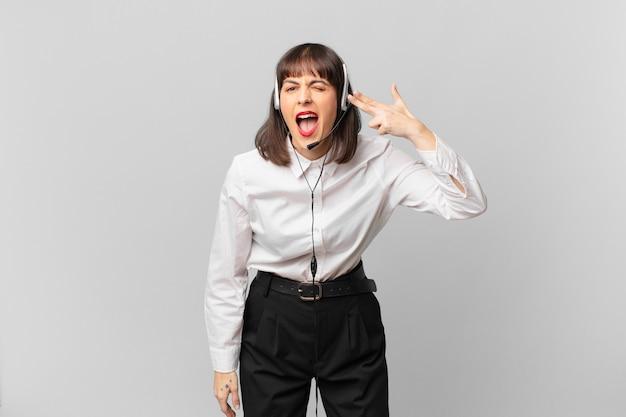 Mulher do operador de telemarketing parecendo infeliz e estressada, gesto suicida fazendo sinal de arma com a mão, apontando para a cabeça
