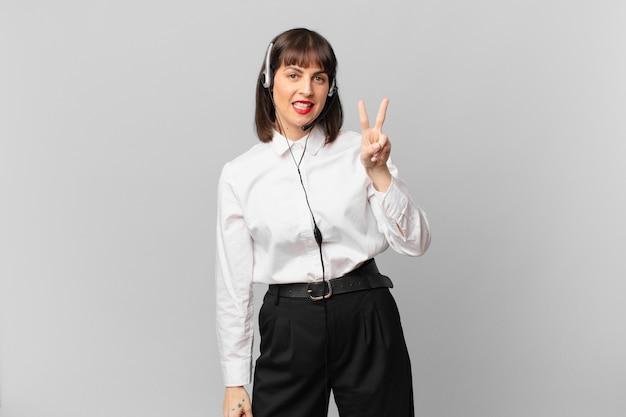 Mulher do operador de telemarketing sorrindo e parecendo feliz, despreocupada e positiva, gesticulando vitória ou paz com uma das mãos
