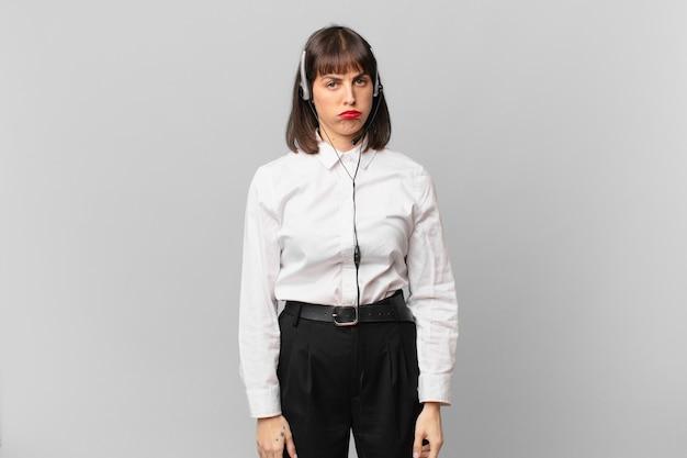 Mulher do operador de telemarketing triste e chorona com uma aparência infeliz, chorando com uma atitude negativa e frustrada