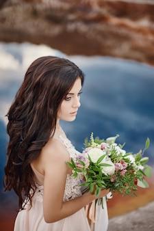 Mulher do retrato com olhos azuis e flores do ramalhete
