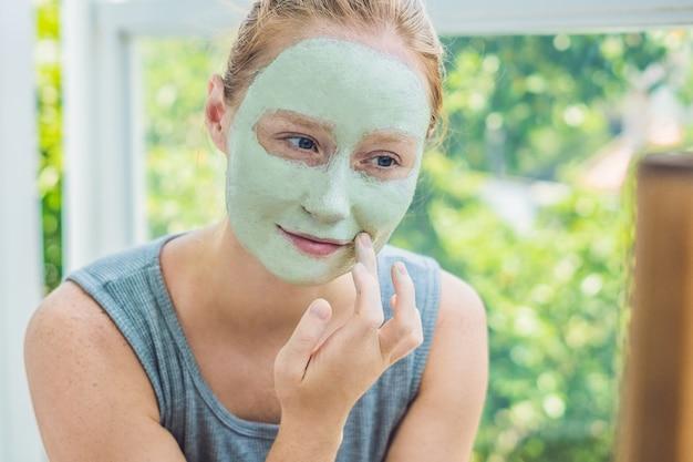Mulher do spa aplicando máscara facial de argila verde