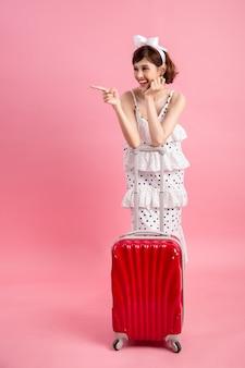 Mulher do turista do viajante na roupa ocasional do verão com a mala de viagem isolada no rosa