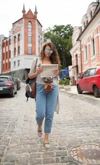 Mulher do turista em óculos de sol da moda e jornal nas mãos dela.