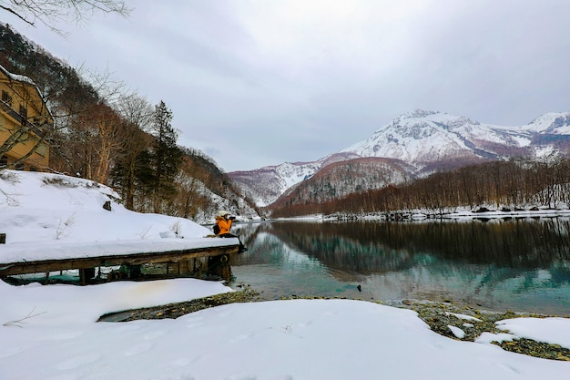 Mulher do turista na montanha da neve com os rios no kamikochi na montanha dos cumes de japão.