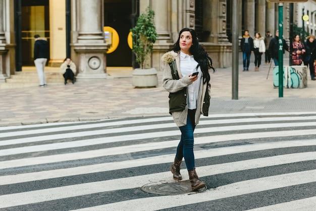 Mulher do turista que cruza uma rua perdida ao consultar um mapa em seu smartphone