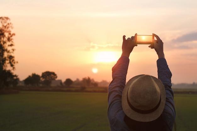 Mulher do turista que toma uma foto com o smartphone no fundo da natureza do por do sol