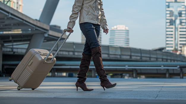 Mulher do viajante com mala de viagem que anda na cidade.