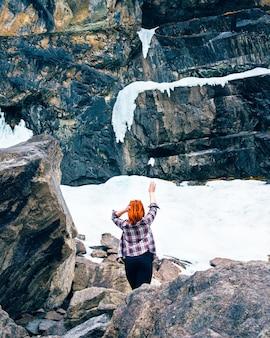 Mulher do viajante da liberdade que está nas montanhas congeladas