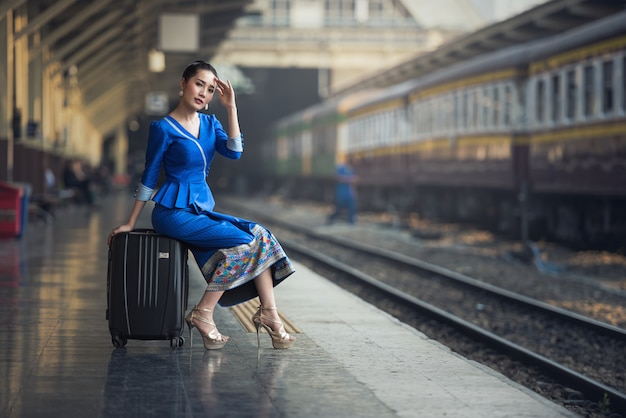 Mulher do viajante do passageiro no curso de espera da estação de trem.