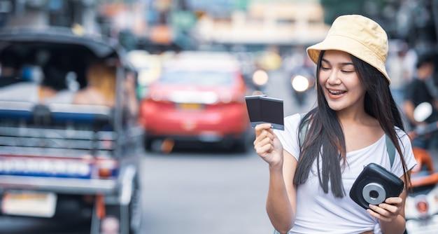 Mulher do viajante que guarda a câmera instantânea e o filme na estrada de khao san, cidade de banguecoque de tailândia.