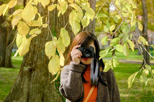 Mulher do viajante que toma a fotografia com sua câmera no parque no dia ensolarado do outono