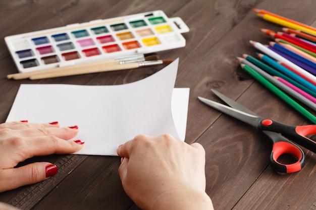 Mulher dobra uma folha de papel para origami