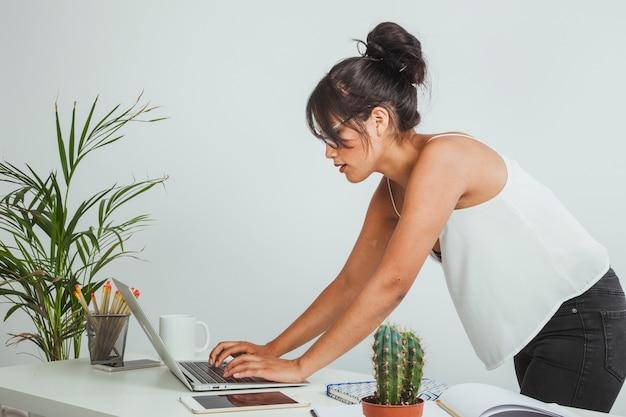 Mulher dobrada digitando no laptop