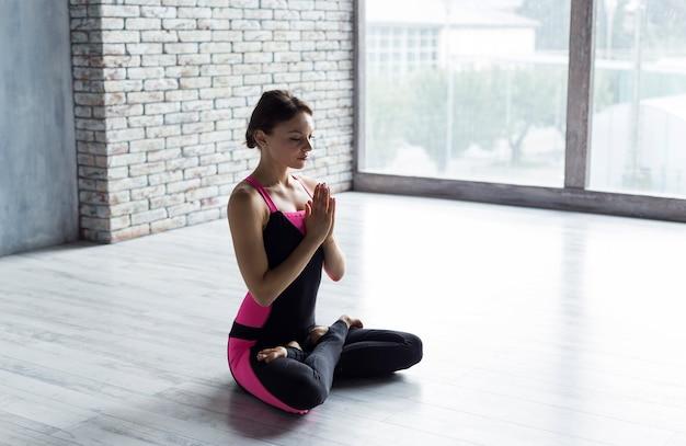 Mulher, dobrando, mãos, em, namaste, ioga posa, enquanto, sentando