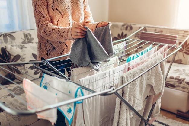 Mulher, dobrando-se recolhendo roupas limpas do secador após lavar em casa