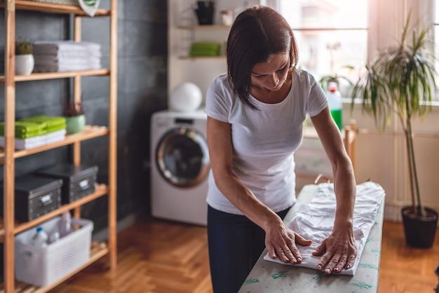 Mulher dobrar roupas na tábua de passar roupa