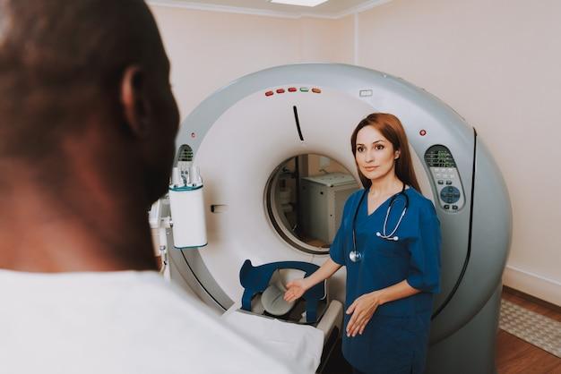 Mulher doc instruindo o homem antes do exame de ressonância magnética