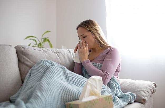 Mulher doente assoar nariz, sentado debaixo do cobertor