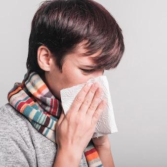 Mulher doente assoar o nariz em papel absorvente contra fundo cinza
