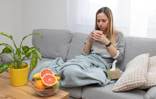 Mulher doente, bebendo chá em sua casa