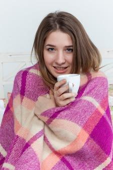 Mulher doente coberta com manta segurando a xícara de chá