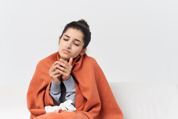 Mulher doente, coberta com um cobertor, senta-se no sofá e é tratada. foto de alta qualidade
