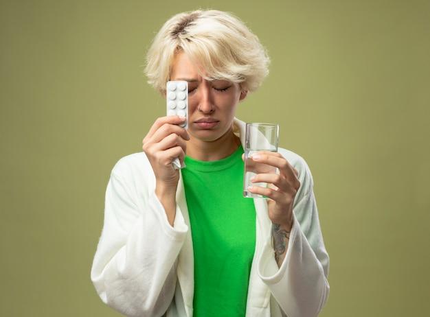 Mulher doente, com cabelo curto, sentindo-se mal, segurando um copo d'água e uma bolha com comprimidos, com os olhos fechados e uma expressão triste em pé sobre um fundo claro