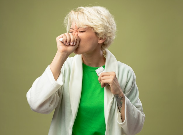 Mulher doente, com cabelo curto, sentindo-se mal segurando um remédio, tossindo em pé sobre um fundo claro