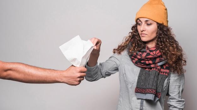 Mulher doente com cachecol em volta do pescoço, segurando o lenço de papel contra o fundo cinza
