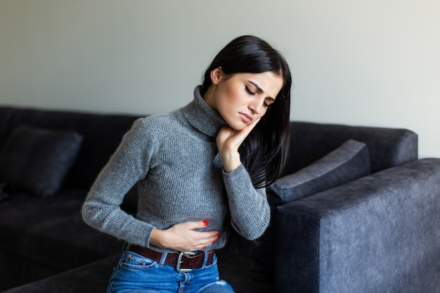 Mulher doente com dor de estômago na sala de estar
