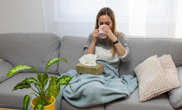 Mulher doente com febre alta, bebendo chá