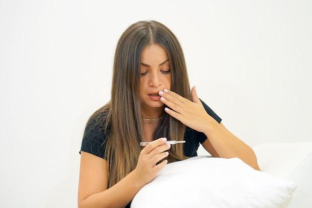 Mulher doente com febre e resfriados, olhando um termômetro sentado em um sofá.