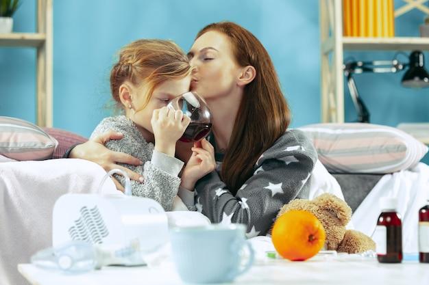 Mulher doente com filha em casa. tratamento em casa. saúde médica.