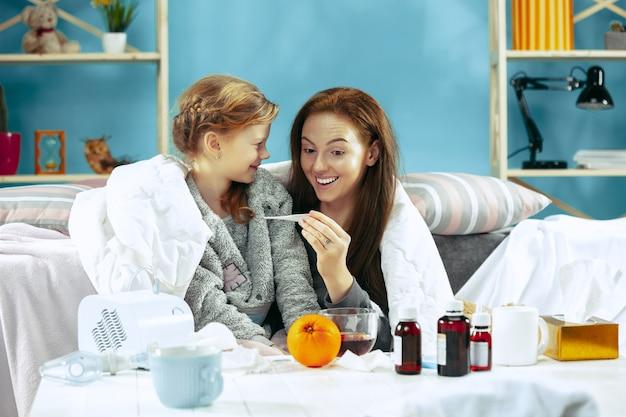 Mulher doente com filha em casa.