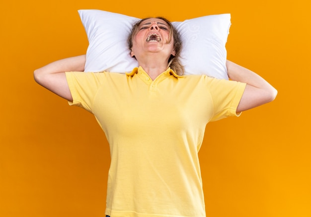 Mulher doente, com gripe e resfriado, com um travesseiro atrás da cabeça sobre uma parede laranja
