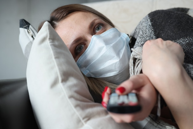 Mulher doente com máscara médica protetora encontra-se no sofá e mantém o controle remoto. conceito de quarentena de pandemia de coronavírus