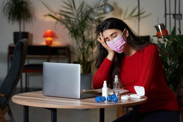 Mulher doente com pílulas e termômetro em uma mesa trabalhando em um laptop em casa em isolamento de quarentena.