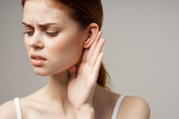 Mulher doente com problemas de audição em camiseta branca de fundo claro