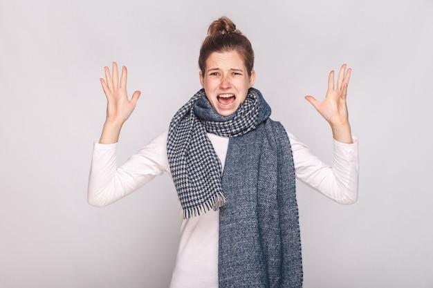 Mulher doente com raiva rugir para a câmera e ter uma aparência indisposta. foto de estúdio