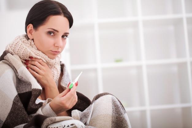 Mulher doente com termômetro.