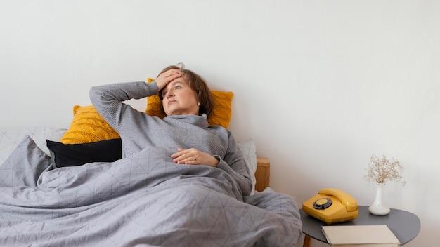 Mulher doente com tiro médio deitada na cama
